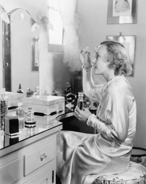 Woman sitting in front of her vanity putting perfume on her eyebrows