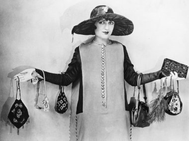 Woman standing with her arms apart wearing handbags