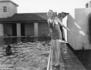Woman next to a pool in her swimming cap and bathing suit