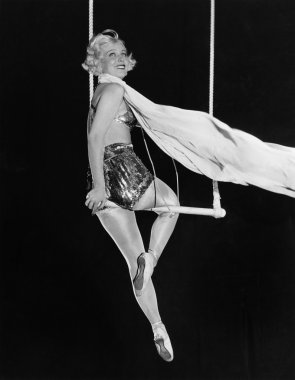 Profile of a female circus performer performing on a trapeze bar