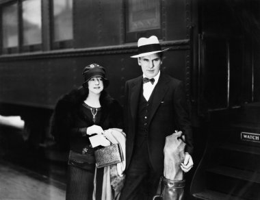 Couple standing at a railroad station platform