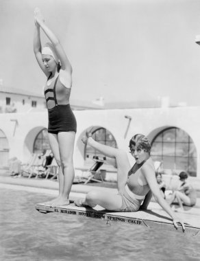 Young woman preparing to dive from a diving platform with another woman sitting beside her