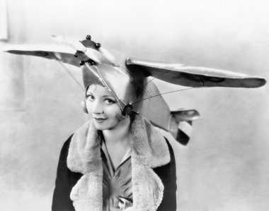 Portrait of a young woman wearing an airplane shaped cap