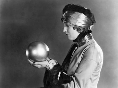 Profile of a woman holding a metal ball