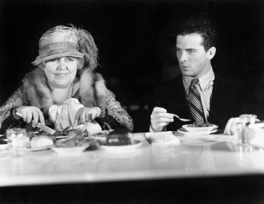Woman and young man sitting at a coffee counter