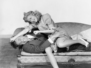 Couple having a playful fight on a couch