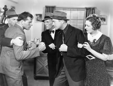 Two men fighting with each other and being held back by a woman and a man