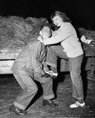 Portrait of a young man helping a young woman board a trailer