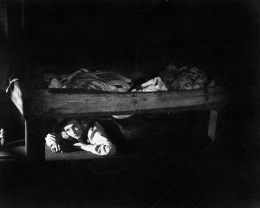 Young woman hiding under the bed