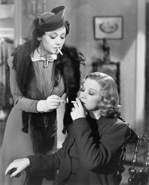 Young woman lighting a cigarette of her friend