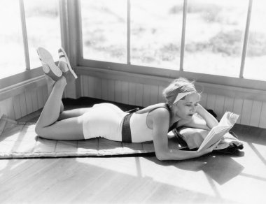 Profile of a young woman lying on a blanket on her stomach and reading a book