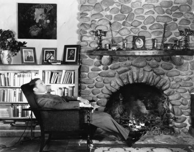 Profile of a young man resting in an arm chair near a fireplace
