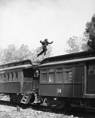 Man leaping across the roof of railroad cars
