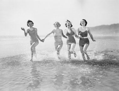 Four women running in water on the beach