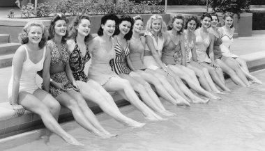 Group of women sitting in a row at the pool side