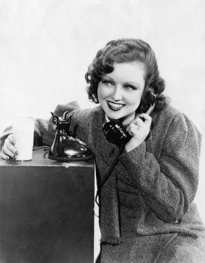 Young woman holding a glass of milk and talking on a rotary phone