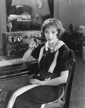 Switchboard operator sitting at telephone switchboard and talking