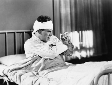 Man sitting on a hospital bed looking feared