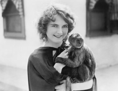 Woman holding a pet monkey in her arms