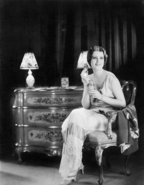 Elegant woman in an evening dress applying perfume to her neck
