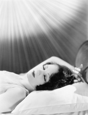 Woman sleeping in a bed with rays of light shining on her