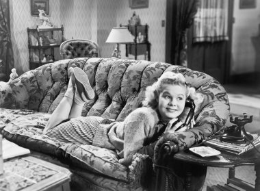 Young woman lying on a sofa in a living room and talking at the phone