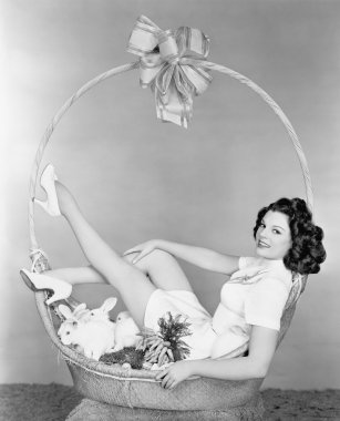 Young woman, looking like a present, sitting in gift basket with bunnies