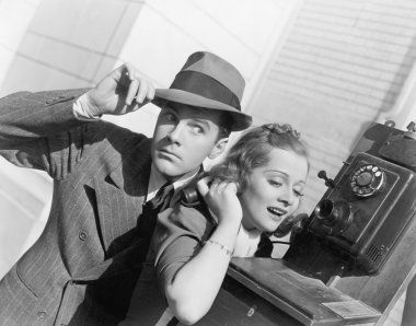 Man and woman listening on an outside telephone