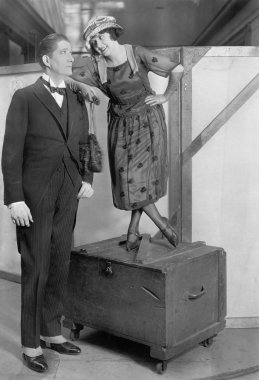 Woman standing on a trunk next to a very tall man
