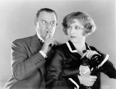 Man telling a woman to be discrete when she is on the telephone