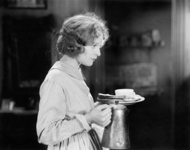 Young woman carrying a pot of coffee and a plate with bread
