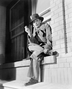 Young woman in men's clothing sitting on a window ledge smoking a pipe