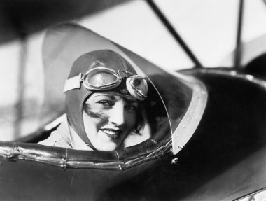 Young woman sitting in a biplane with hat and gargles