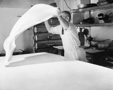 Baker throwing dough through the air