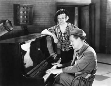 Man playing the piano while a woman is listening