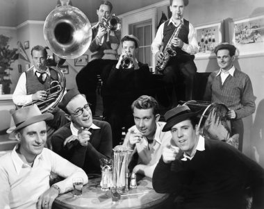 Group of men sitting in a diner with musicians behind them