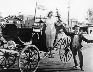 Man helping a woman get out of a wagon
