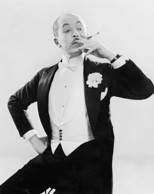 Man in white tie posing with a cigarette