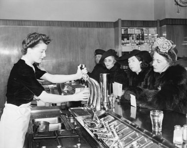 Three woman and a man sitting in a soda fountain