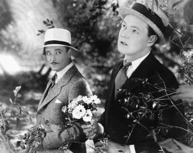 Two men standing in a garden holding a bouquet of flowers