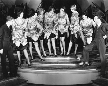 A chorus line of women showing off their legs to two men