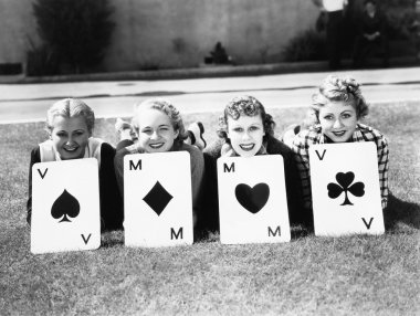 Four women are well suited to lay on the grass with playing cards in front of them