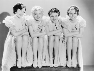 Four woman sitting together and posing