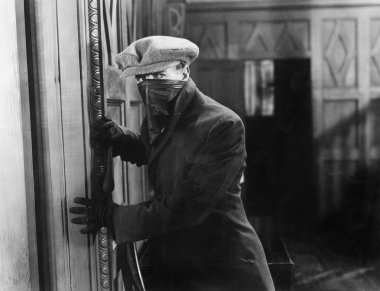 Burglar with mask in a home