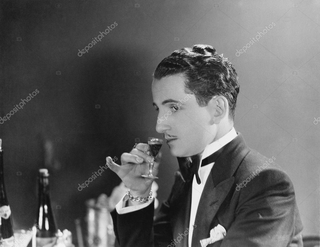 Man drinking glass of liqueur