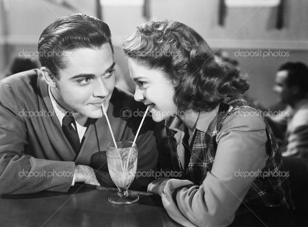 Couple in a restaurant looking at each other and sharing a milk shake with two straws