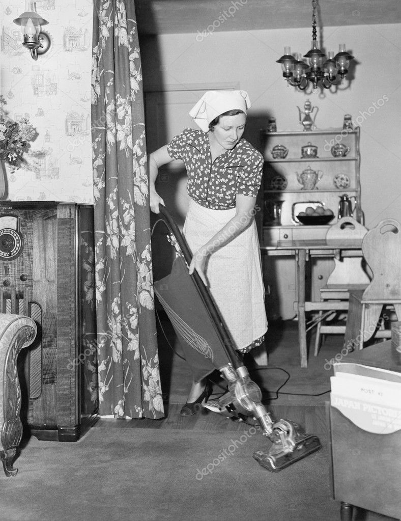 Woman Doing Housework With A Vacuum Cleaner Stock Photo