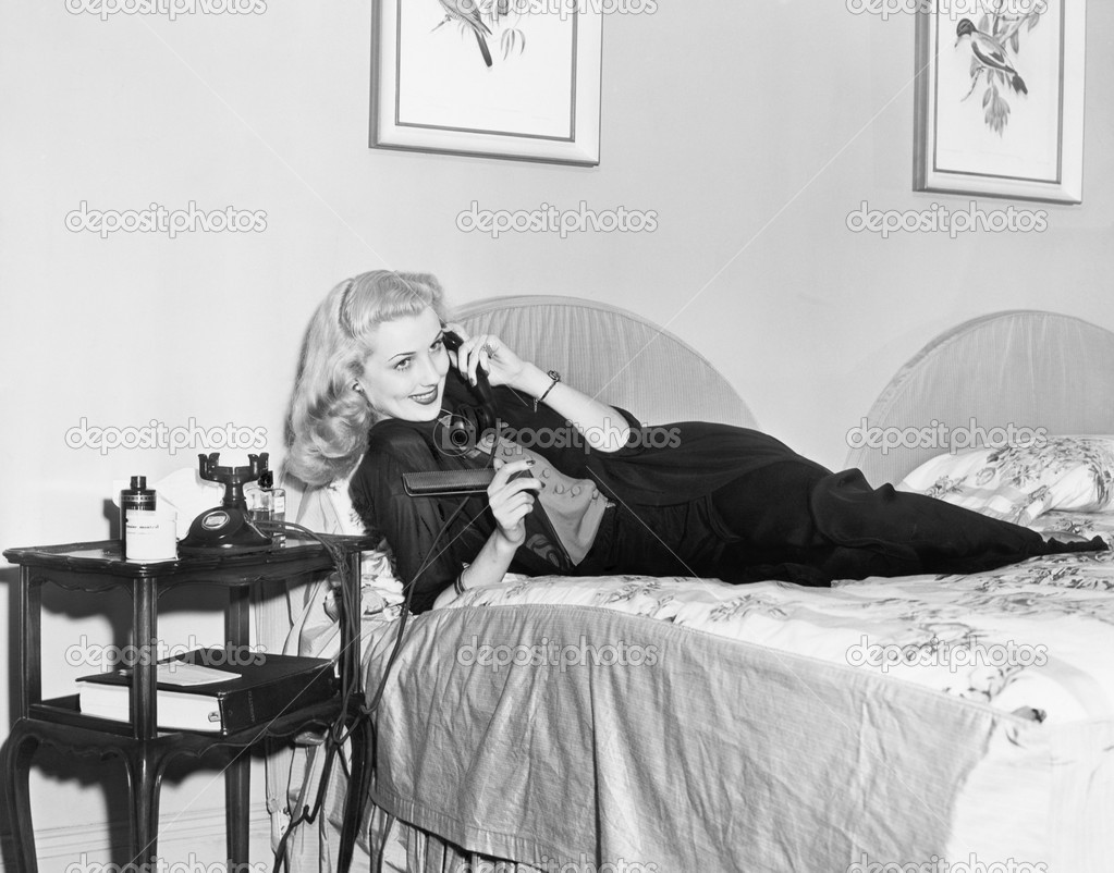 jeune femme allong e sur son lit dans la chambre coucher et parler au t l phone photographie. Black Bedroom Furniture Sets. Home Design Ideas