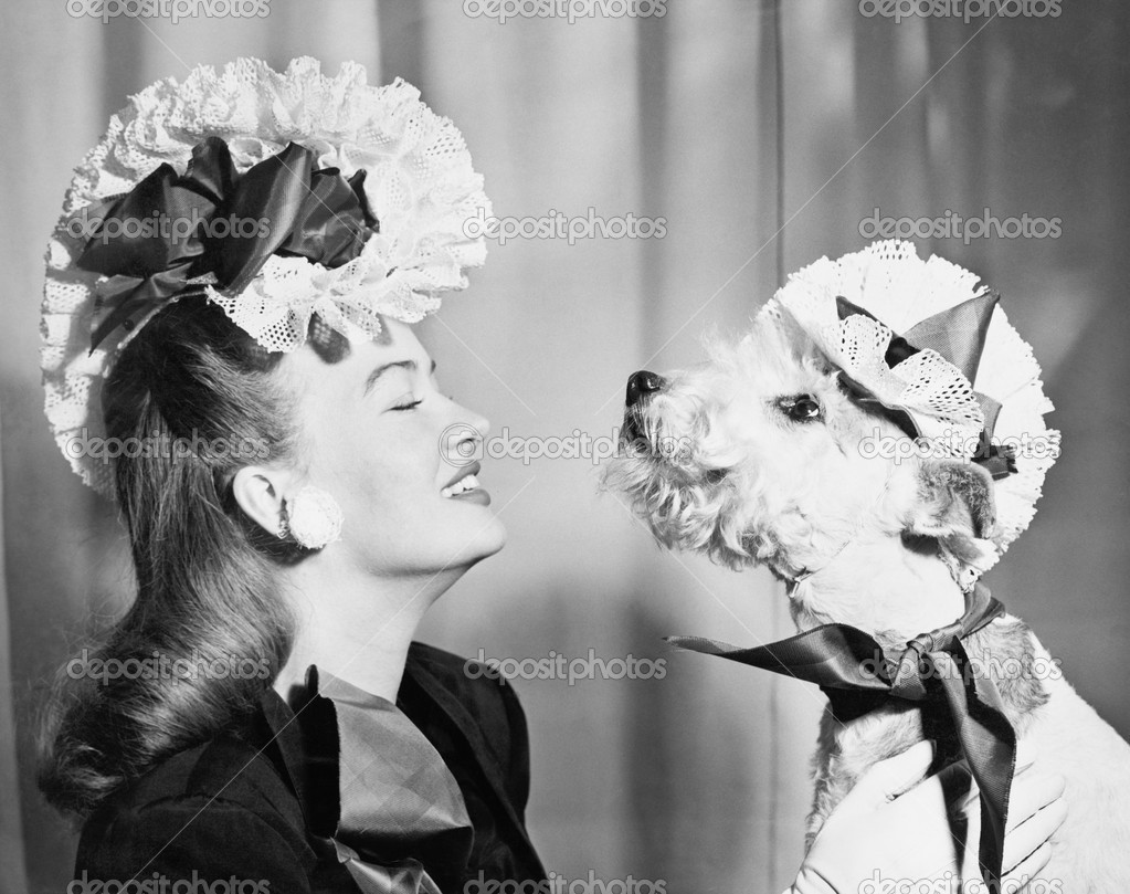 Young woman with her dog who is wearing the same hat