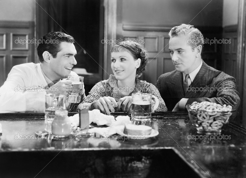 Two men and a woman sitting at a bar drinking beers